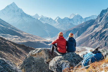 Couple resting on the Everest Base Camp trekking route near Dughla 4620m. Backpackers left Backpacks and trekking poles and enjoying valley view with Ama Dablam 6812m peak and Tobuche 6495m Wall mural