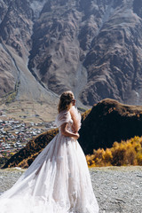 noise effect, selective focus: attractive girl dressed in chic long wedding dress on a background of mountain rocks, model posing for promotional photos for wedding salon
