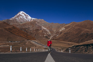 young attractive man with a beard dressed in a red jacket climbs the asphalt road on the slopes of the Caucasus Mountains against the backdrop of Mount Kazbek