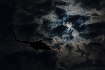 Poster Helicopter Helicopter on full moon background, hidden flight at night. Silhouette of helicopter flying in dark in stormy weather. Rescue Service and Search. Aviation in lunar sky. Moonlight