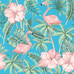 Tropical pink hibiscus and flamingo floral green palm leaves seamless pattern blue background. Exotic jungle wallpaper.