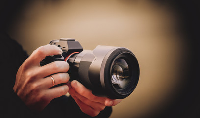 A man holds a camera in his hands and takes pictures, tinted photo