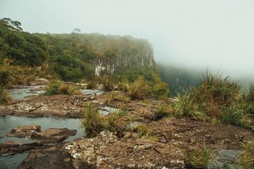 Creek on waterfall edge with steep rocky cliffs