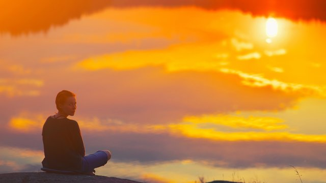 Beautiful woman sits in a pose of a lotus on high place with amazing view of the lake sunset practice yoga meditation Kundalini energy mindset intuition prana. Solitude harmony mental freedom concept