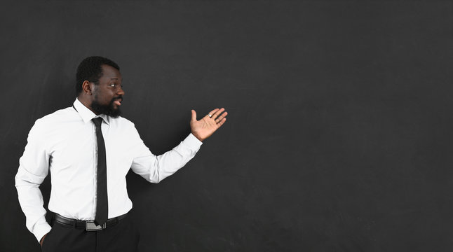 African-American teacher near blackboard in classroom
