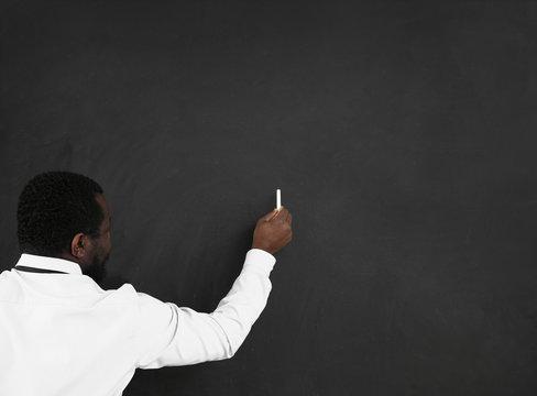 African-American teacher writing on blackboard in classroom