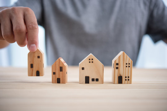 man hand choosing mini wood house model from model on wood table,  Planning to buy property. concept of Choose the best.