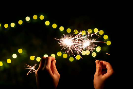 Girl enjoy playing with a small sparkler hand fireworks, celebrating in Christmas and New Year  festival.