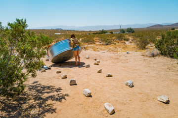 A woman in her twenties drains a stock tank basin in the desert of Joshua Tree, California