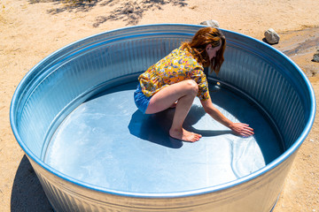 A woman in her twenties cleans a stock tank basin in the desert of Joshua Tree, California