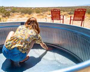 A woman in her twenties cleans a stock tank pool in the desert of Joshua Tree, California