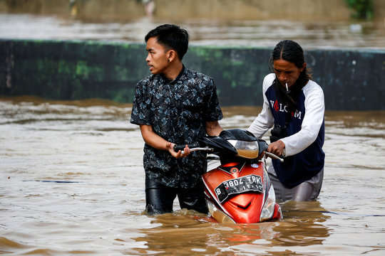 Men push a motorcycle through floodwaters at the Jatinegara area after heavy rains in Jakarta