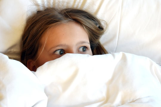 A girl looks out from under the blankets. Frightened face of the child.