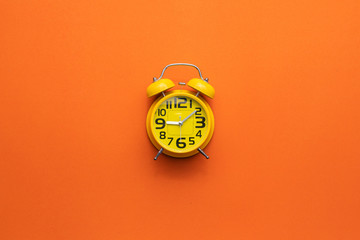 Yellow alarm clock on the middle of orange background