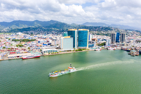 Aerial view of city of Port of Spain, the capital city of Trinidad and Tobago. Skyscrapers of the downtown and a busy sea port with commercial docks and passenger catamarans