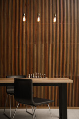 Modern table with chess near wooden wall