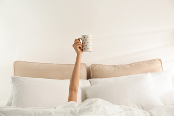 Woman with cup of coffee in bed, closeup. Lazy morning