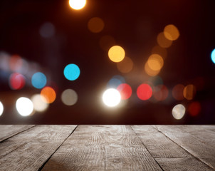 Empty wooden surface against blurred lights. Bokeh effect