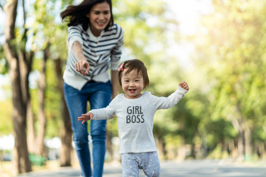 Young cute happy little Asian toddler girl running in park with mother. Mom taking care daughter by following and hold child carefully. Kid smiling enjoy learning to walk and run, family relation.