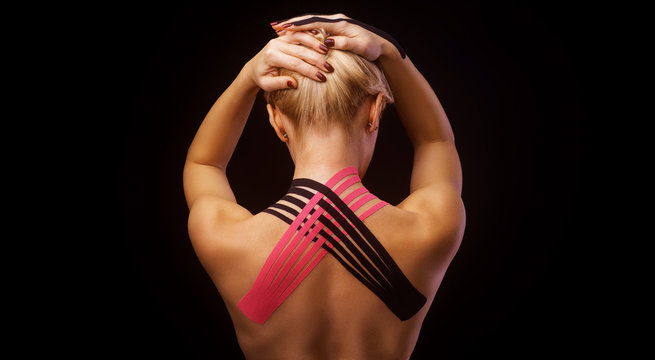 Beautiful young woman with kinesiotape on her neck area after injury on black background