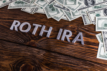words ROTH IRA laid on wooden surface with metal letters and us dollar banknotes
