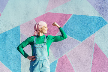 Portrait of woman with pink headscarf, has cancer. Show the arm as a signal of strength