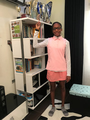 Iyeneobong Essien,13-year-old golf prodigy points at her trophies as she poses for a photograph at home in Abuja