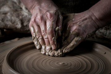 Hand craft making pottery on wheel. Female hands mold ceramic plate from clay