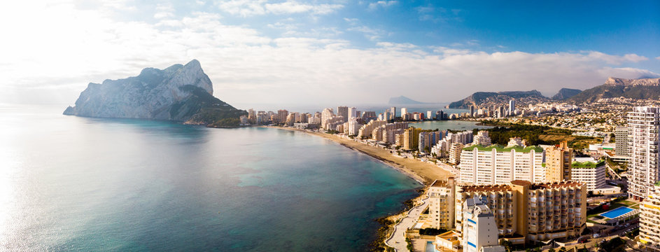 Aerial view of Calpe city in Alicante, Spain, at sunrise. La Fossa beach is in the foreground and de Ifach Penon rock in the background.