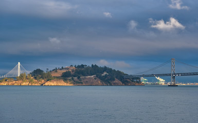 Fotomurales - Bay Bridge Past Treasure Island in Afternoon LIght on Stormy Day