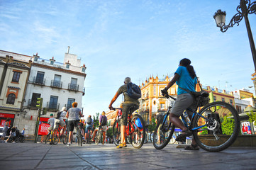 Tourists on bike tour through Triana neighborhood in Seville, Andalusia, Spain
