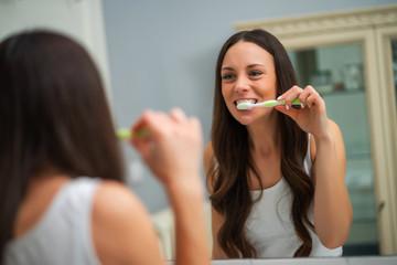 Young woman is brushing her teeth in bathroom. Fototapete