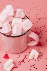 pink mug on a pink background filled with marshmallows in the form of hearts. valentine's day...