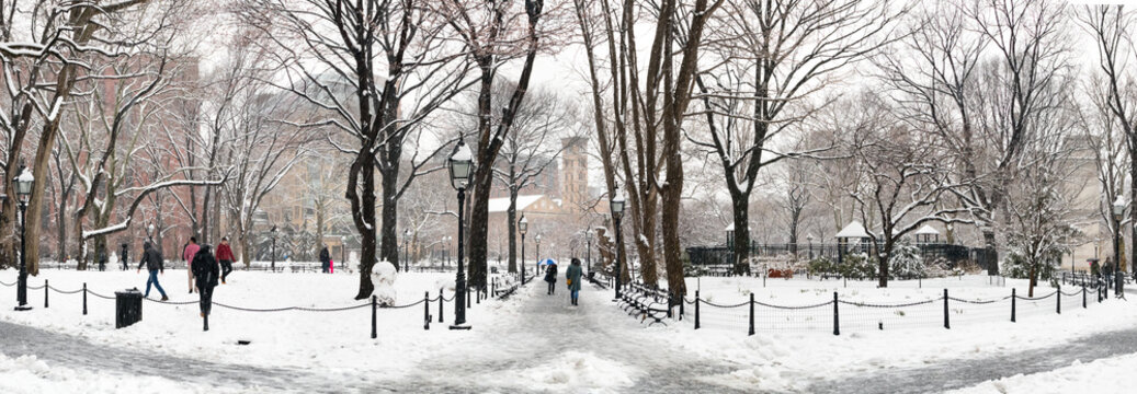 Panoramic winter scene with people walking through the snow covered landscape of Washington Square Park in New York City