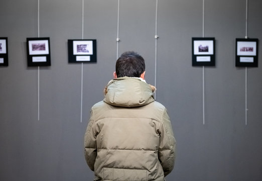 Adult Caucasian man visiting exhibition in modern art gallery
