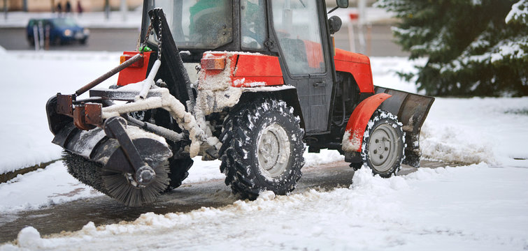 Red tractor clearing snow on footpath, with snow plow and rotating brush. Municipal service removing snow from sidewalk. Road sweeping vehicle with plough brush equipment