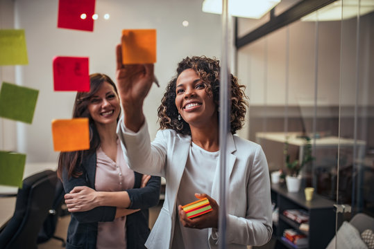 Creative businesswoman writing on sticky notes on a glass wall, female colleague looking.
