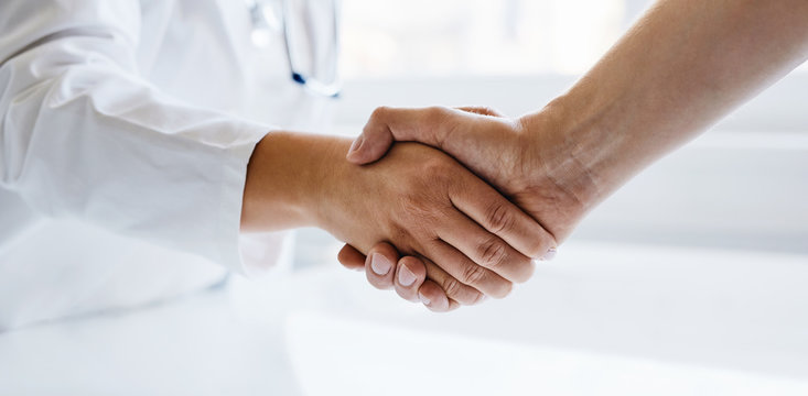 Female doctor shaking hands with man in medical office