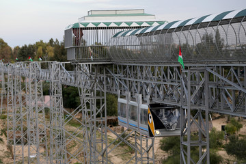 Palestinians enjoy a ride in an amusement park suspension railway, in the southern Gaza Strip