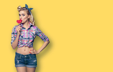Surprised woman eating heart shape lollipop. Girl in pin up cloth. Retro fashion and vintage concept picture. Yellow color background. Copy space for some advertise slogan or text.