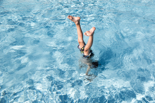 A boy does a handstand in the swimming pool