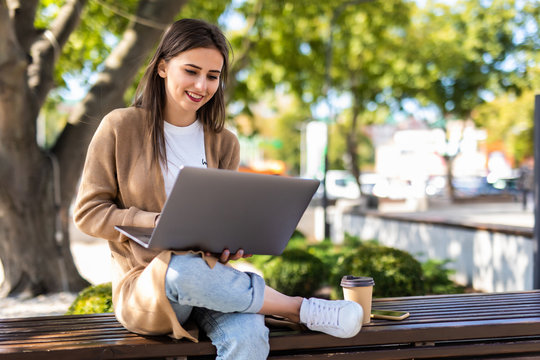 Young beautiful business woman working on a laptop sitting on the bench in the street