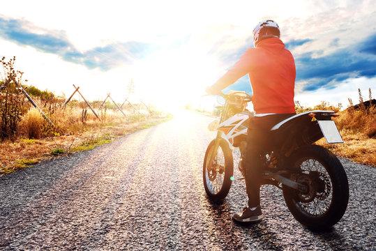 Junger Motorradfahrer auf einer Straße schaut in den Sonnenuntergang
