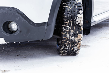an unadorned picture of winter car wheel with metal spikes on snow close-up