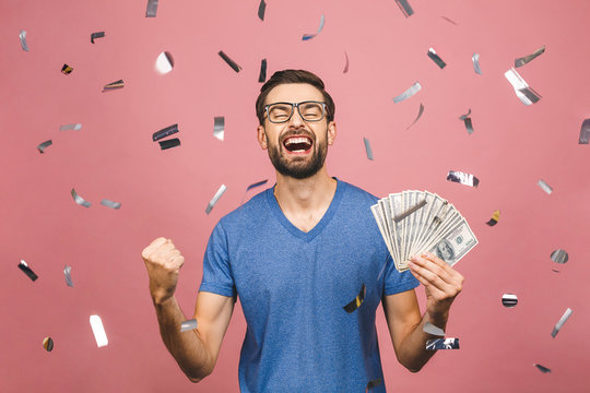Happy winner! Young rich man in casual t-shirt holding money dollar bills with surprise isolated over pink background.