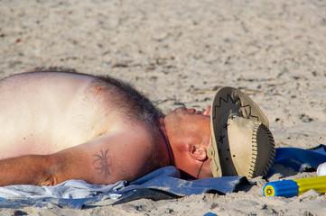 a fat man at the beach