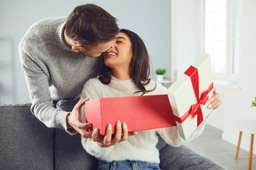 Valentine's day. A young couple gives a gift in a room
