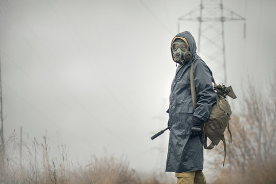 Soldier in gas mask and raincoat with a rifle walking on the empty road concept.