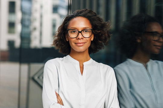 Portrait of a beautiful businesswoman in glasses standing outdoors and looking away. Young entrepreneur near office building.