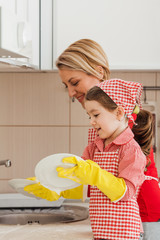 Mother and child washing dishes together